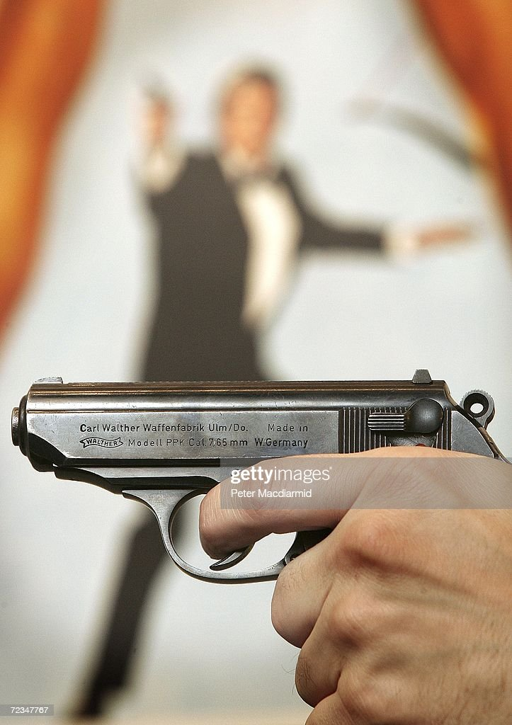 A Walther PPK handgun is held up infront of a poster of the film 'For Your Eyes Only' during promotion of a sale of weapons from James Bond films on November 2, 2006 in London. Actor Daniel Craig will play Bond in 'Casino Royale' the 21st film made from author Ian Fleming's books. Christie's Film and Entertainment sale takes place on December 5, 2006.