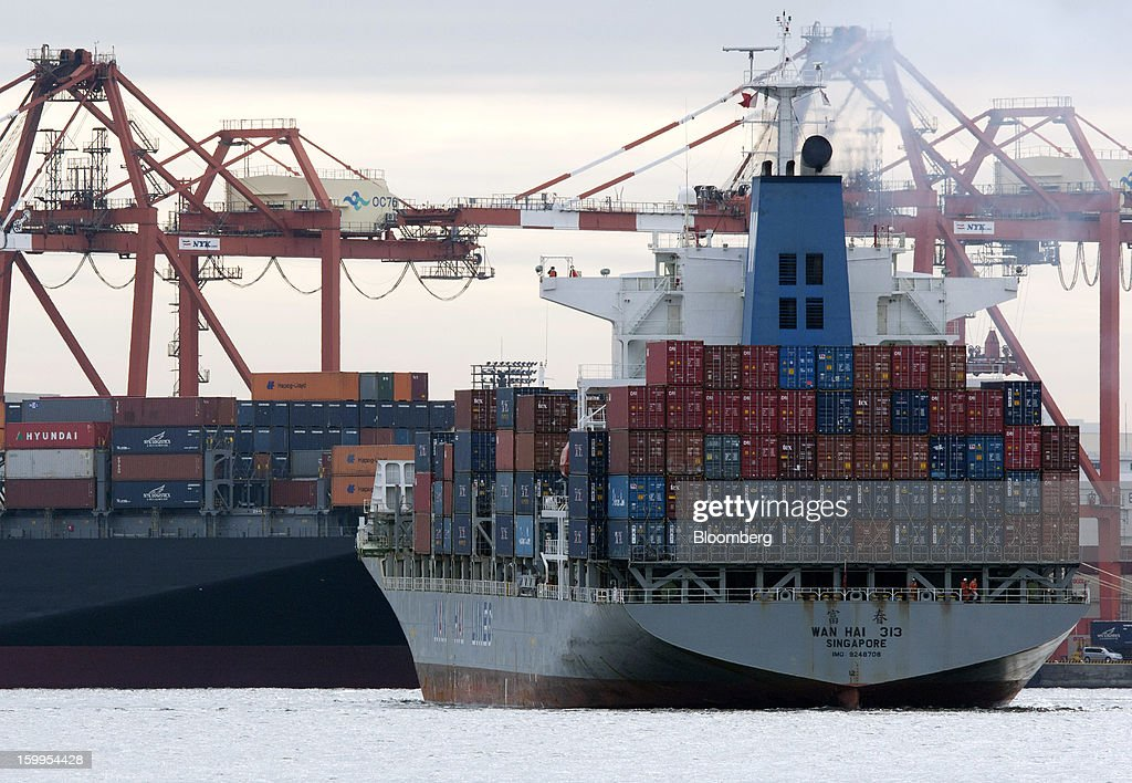 A Wan Hai Lines Ltd. container ship, right, enters a port as a Nippon Yusen K.K. container ship is moored in Tokyo, Japan, on Wednesday, Jan. 23, 2013. Japan's exports fell more than analysts forecast and the annual trade deficit swelled to a record, bolstering the case for Prime Minister Shinzo Abe to weaken the yen even as trade tensions mount. Photographer: Tomohiro Ohsumi/Bloomberg via Getty Images