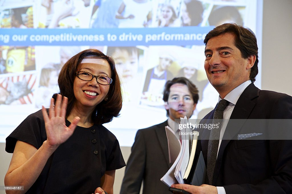 Wan Ling Martello, chief financial officer of Nestle SA, left, and Roddy Child-Villiers, investor relations director at Nestle SA, right, pose for a photograph following a news conference to announce the company's results in Vevey, Switzerland, on Thursday, Oct. 17, 2013. Nestle SA, the world's biggest food company, reported nine-month sales that were below its full-year target rate, highlighting the difficult environment faced by the makers of consumer products. Photographer: Gianluca Colla/Bloomberg via Getty Images