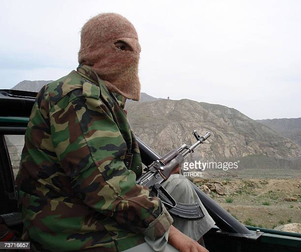 In this photograph taken 26 March 2007 a masked Pakistani tribesman patrols the mountain area of Wana in the South Waziristan tribal territory...