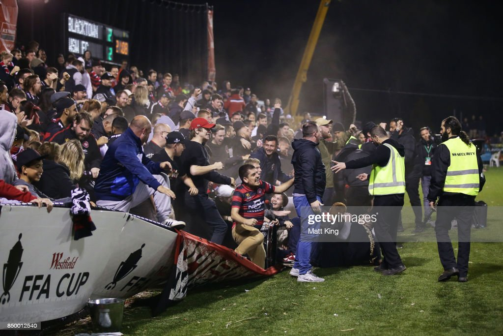 Wanderers fans celebrate the extra time goal to Oriol Riera of the Wanderers as the perimeter fence gives way during the FFA Cup Quarterfinal match between Blacktown City and the Western Sydney Wanderers at Lily Football Centre on September 20, 2017 in Sydney, Australia.