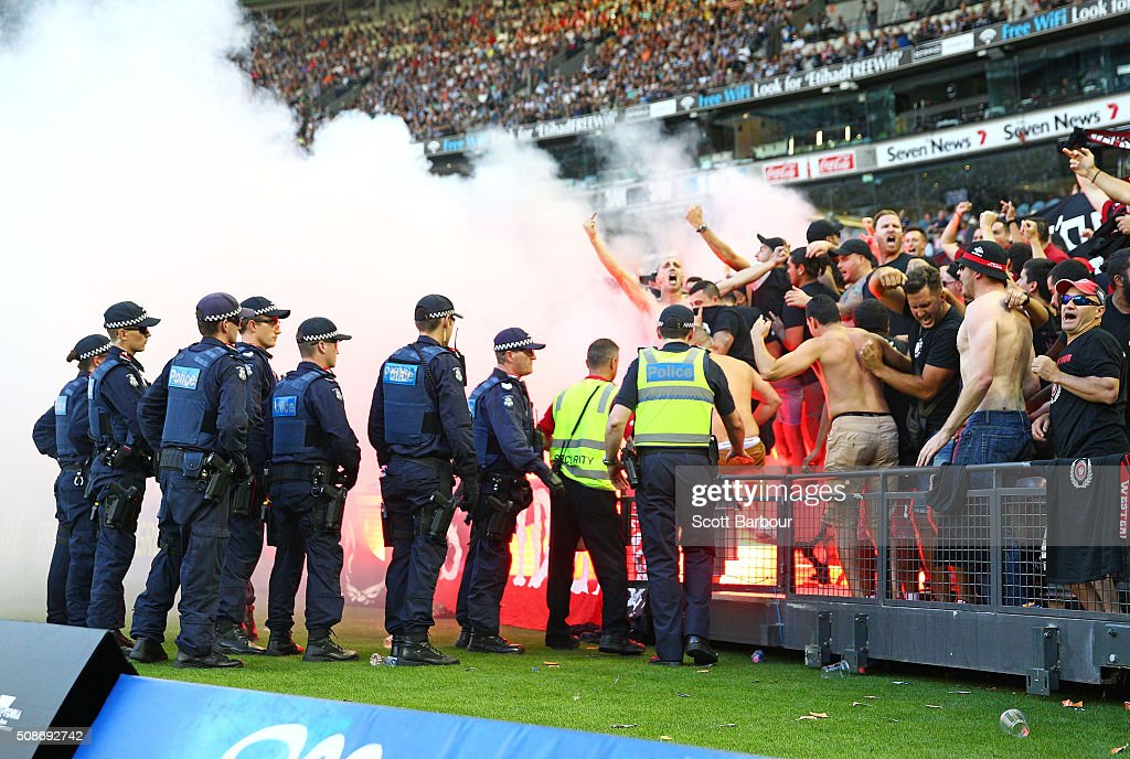 Wanderers fans in the crowd let off flares as police officers look on during the round 18 A-League match between the Melbourne Victory and Western Sydney Wanderers at Etihad Stadium on February 6, 2016 in Melbourne, Australia.