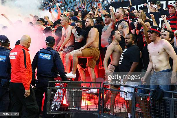 Wanderers fans in the crowd let off flares as police officers look on during the round 18 ALeague match between the Melbourne Victory and Western...