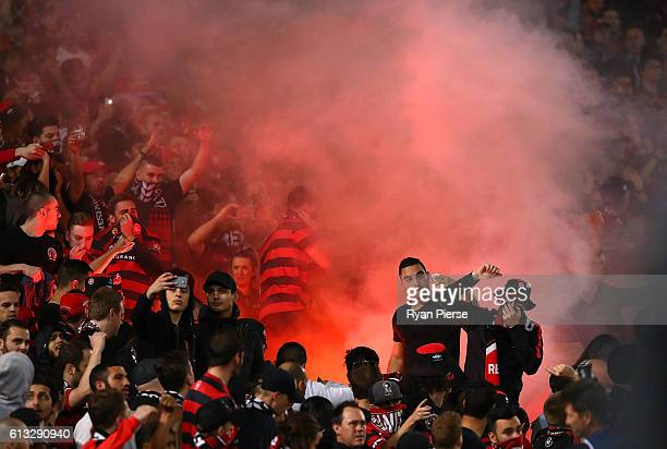 Wanderers fans look on as a flare is lit during the round one ALeague match between the Western Sydney Wanderers and Sydney FC at ANZ Stadium on...