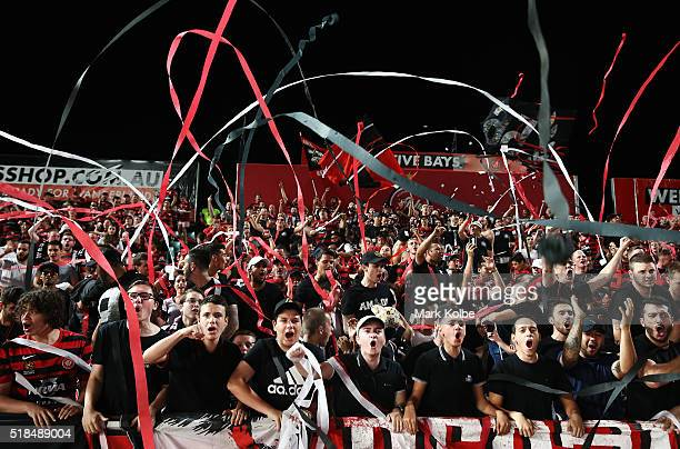 Wanderers supporters in the 'Red and Black Block' throw streamers as they cheer their team onto the field during the round 26 ALeague match between...