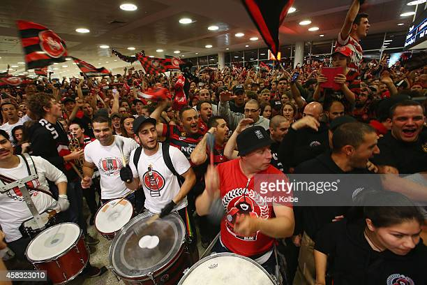 Wanderers supporters sing as they wait in the arrivals hall for the Western Sydney Wanderers arrival at Sydney International Airport from Saudi...