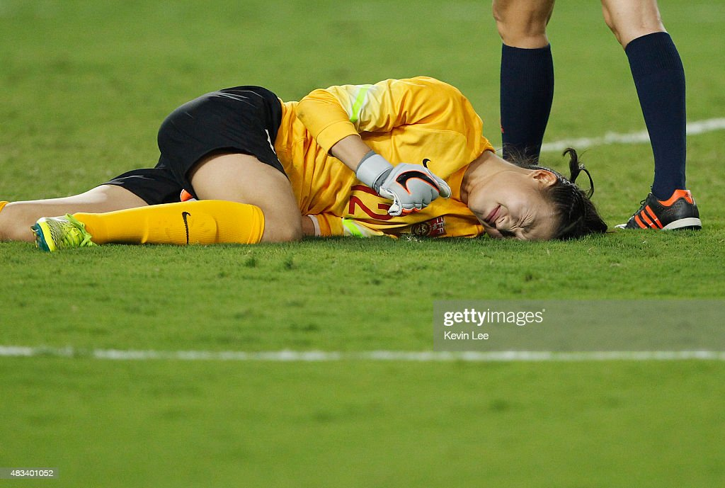 Wang Fei of China PR lies on the ground after a collision during the EAFF East Asian Cup 2015 final round against Japan at the Wuhan Sports Center...