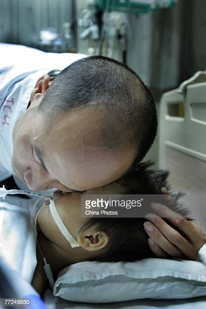 Wang Haijun father of Chinese girl Wang Fei who is in critical condition after a traffic accident hugs his daughter in the ICU of Shenzhen People's...