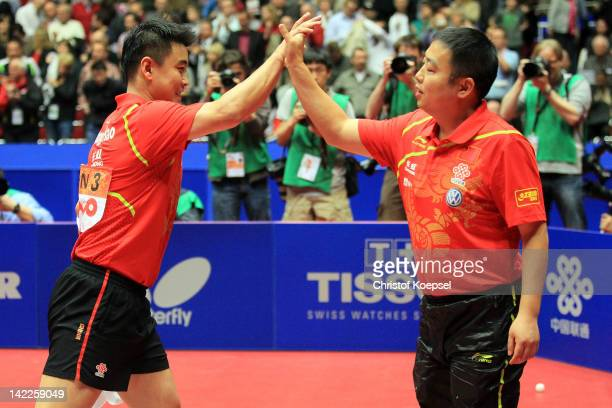 Wang Hao of China celebrates with coach Lui Guoliang of China after winning the LIEBHERR table tennis team world cup 2012 championship division men's...