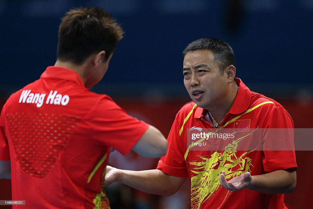 Wang Hao of China talks with coach <a gi-track='captionPersonalityLinkClicked' href=/galleries/search?phrase=Liu+Guoliang&family=editorial&specificpeople=655363 ng-click='$event.stopPropagation()'>Liu Guoliang</a> during his Men's Singles Table Tennis fourth round match against Ning Gao of Singapore on Day 3 of the London 2012 Olympic Games at ExCeL on July 30, 2012 in London, England.