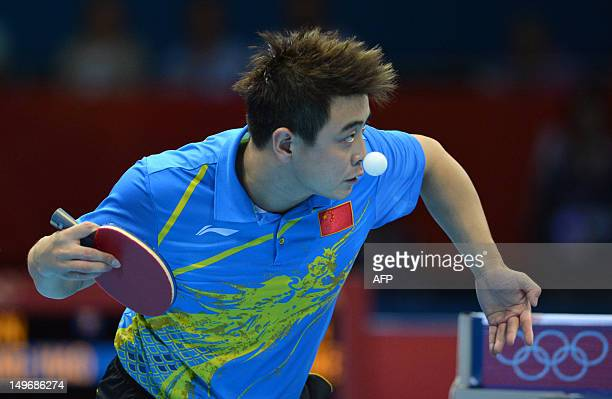 Wang Hao of China watches the ball as he serves during his table tennis men's gold medal singles match against compatriot Zhang Jike for the London...