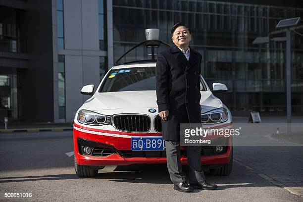Wang Jing senior vice president of Baidu Inc poses for a photograph in front of the company's autonomous car at the company's headquarters in Beijing...