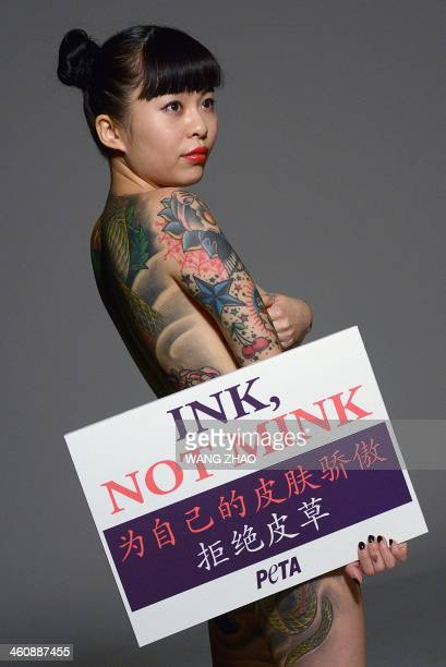 Wang Ke a Chinese tattoo artist shows her tattoos as she holds a placard saying 'Ink not mink Be proud of your own skin Don't wear fur' during an...