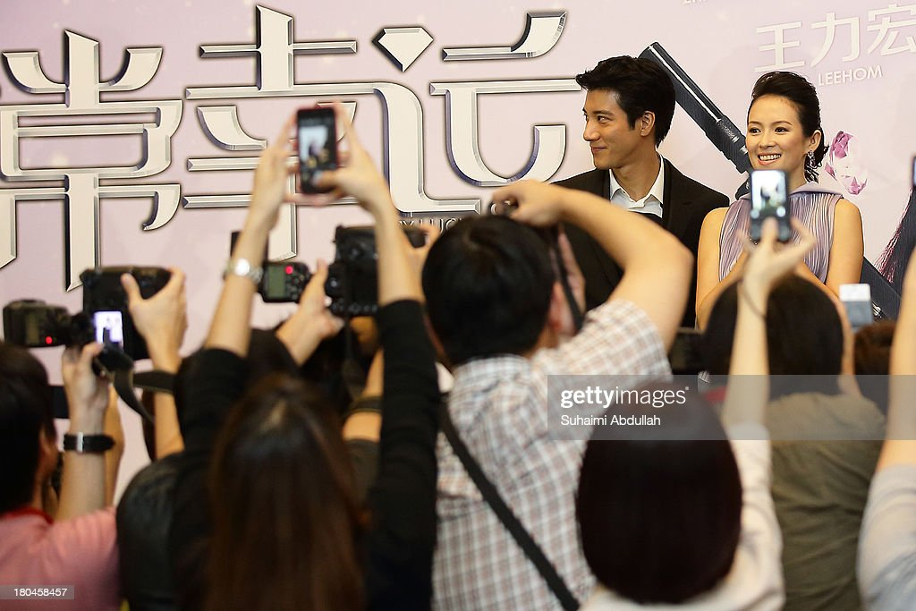 Wang Lee Hom and Zhang Ziyi pose for photographs on stage during the media conference of the movie premiere of 'My Lucky Star' at the ArtScience Museum at Marina Bay Sands on September 13, 2013 in Singapore.