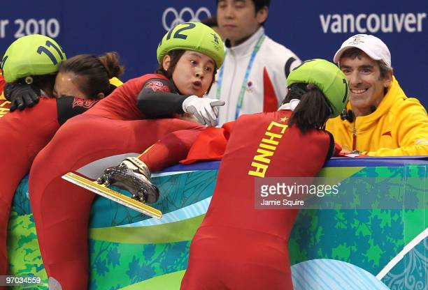 Wang Meng of China reacts after cutting the face of teammate Zhang Hui with the blade of her ice skate after Team China won the gold medal in the...