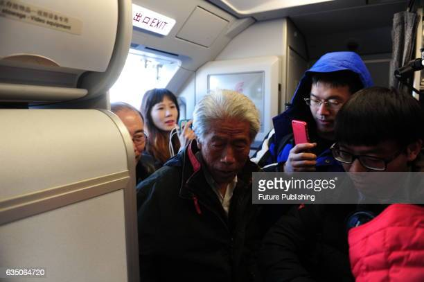 Wang Qi center who has left China for 54 years boards a flight from Beijing to his hometown in Xianyang on February 11 2017 in Shaanxi Beijing China...
