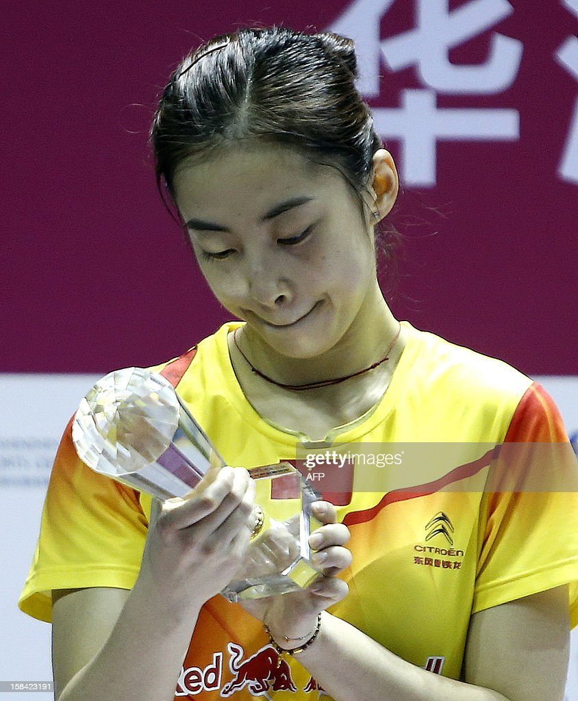 Wang Shixian of China admires her trophy during the award ceremony after losing to compatriot Li Xuerui in the women's singles final match of the 2012 BWF Superseries Finals in Shenzhen, south China's Guangdong province on December 16, 2012. Li beat Wang 21-9, 15-4 (retired) for the title.