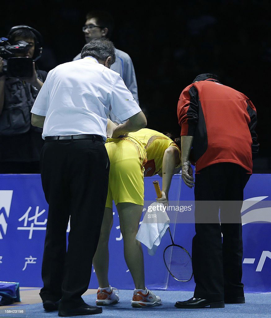 Wang Shixian of China gets her back checked by a physician during the final match against compatriot Li Xuerui in the women's singles of the 2012 BWF Superseries Finals in Shenzhen, south China's Guangdong province on December 16, 2012. Li beat Wang 21-9, 15-4 (retired) for the title. AFP PHOTO