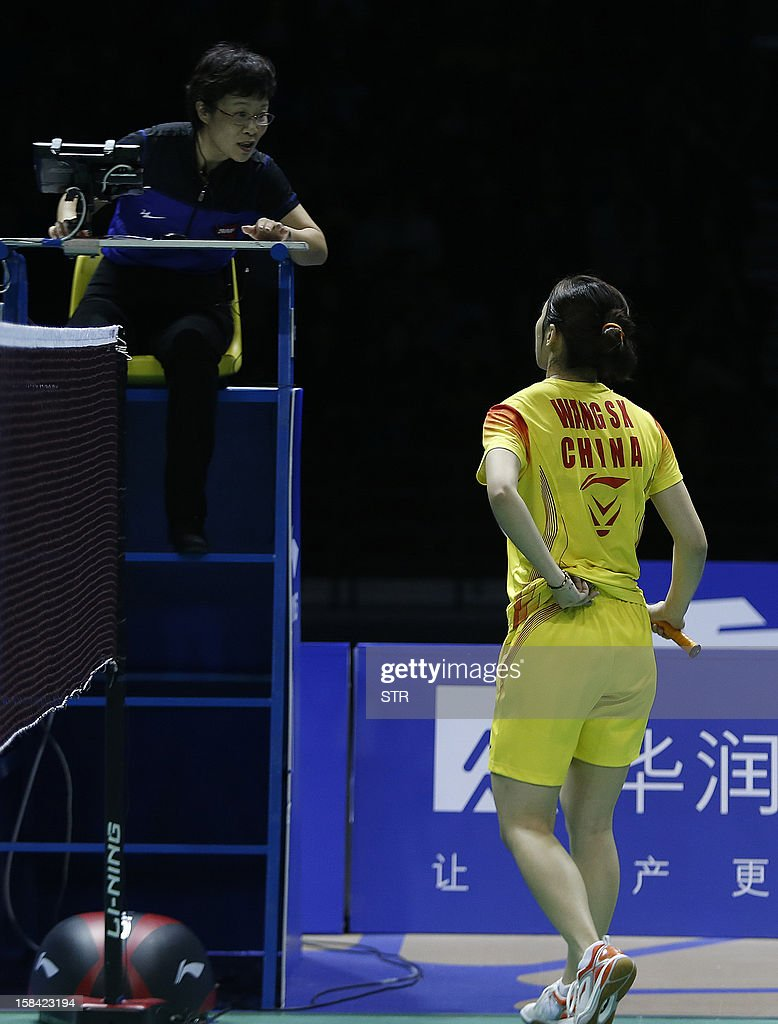 Wang Shixian of China reports to the umpire of her back pain during the final match against compatriot Li Xuerui in the women's singles of the 2012 BWF Superseries Finals in Shenzhen, south China's Guangdong province on December 16, 2012. Li beat Wang 21-9, 15-4 (retired) for the title.