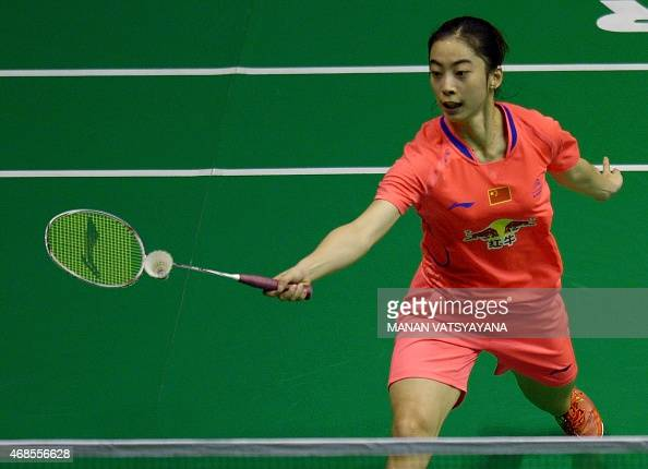Wang Shixian of China returns a shot against Spain's Carolina Marin during their women's singles semifinal match at the 2015 Malaysia Open Badminton...