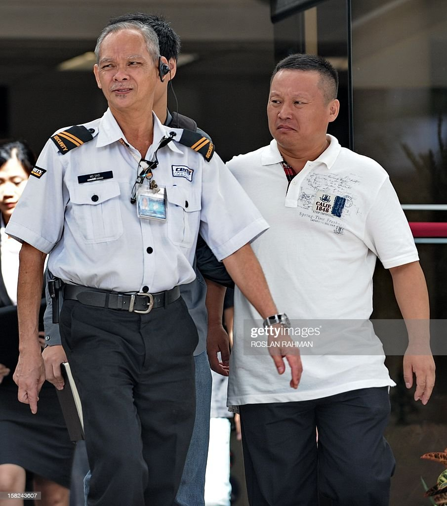 Wang Xianjie (R), 39, one of four Chinese bus drivers facing possible jail for instigating Singapore's first industrial strike in 26 years, leaves the subordinate courts in Singapore on December 12, 2012. Four Chinese bus drivers facing possible jail were given more time on December 12 to explore their legal options and were told to report again on December 19 for a new pre-trial conference. AFP PHOTO / ROSLAN RAHMAN