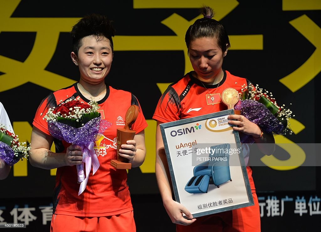 Wang Xiaoli (R) and Yu Yang (L) of China celebrate on the podium after beating compatriots Bao Yixin and Zhong Qianxin in the women's doubles final at the China Open badminton tournament in Shanghai on November 17, 2013. Wang and Yu won 21-13, 21-7. AFP PHOTO/Peter PARKS