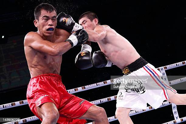 Wang Xin Hua of China throws a punch at Mohamad Nor Rizan of Singapore during the Super Bantamweight bout at Marina Bay Sands on May 5 2012 in...