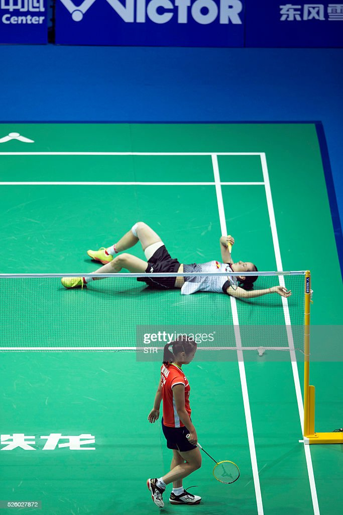 Wang Yihan (top) of China falls during the women's singles quarter-final match against Nozomi Okuhara of Japan at the 2016 Badminton Asia Championships in Wuhan, central China's Hubei province on April 29, 2016. / AFP / STR
