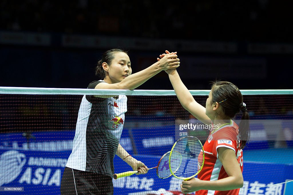 Wang Yihan (L) of China shakes hands with Nozomi Okuhara of Japan after winning their women's singles quarter-final match at the 2016 Badminton Asia Championships in Wuhan, central China's Hubei province on April 29, 2016. / AFP / STR