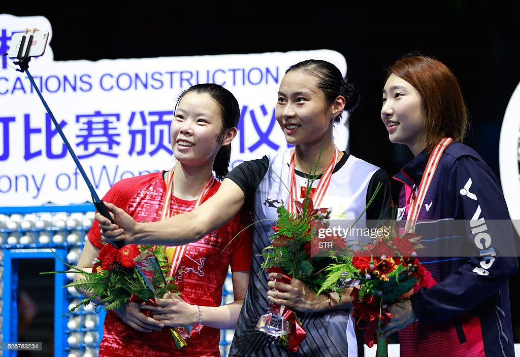 Wang Yihan (C) of China uses a selfie stick to take photos with the runner-up Li Xuerui (L) of China and the third place Sung Ji Hyun of South Korea on the podium after winning the women's singles final match at the 2016 Badminton Asia Championships in Wuhan, central China's Hubei province on May 1, 2016. / AFP / STR / China OUT