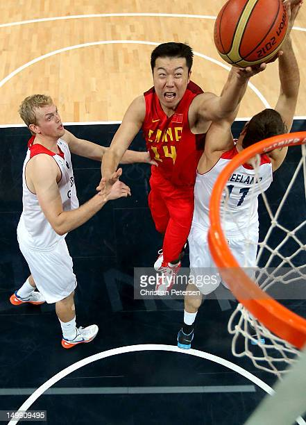 Wang Zhizhi of China drives for a shot attempt against Dan Clark and Joel Freeland of Great Britain during the Men's Basketball Preliminary Round...