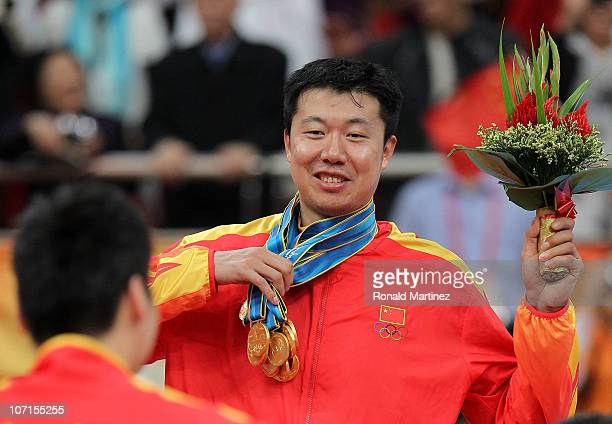 Wang Zhizhi of China is given all the medals by his teammates to wear after China wins the gold medal by defeating South Korea 7771 in the men's gold...