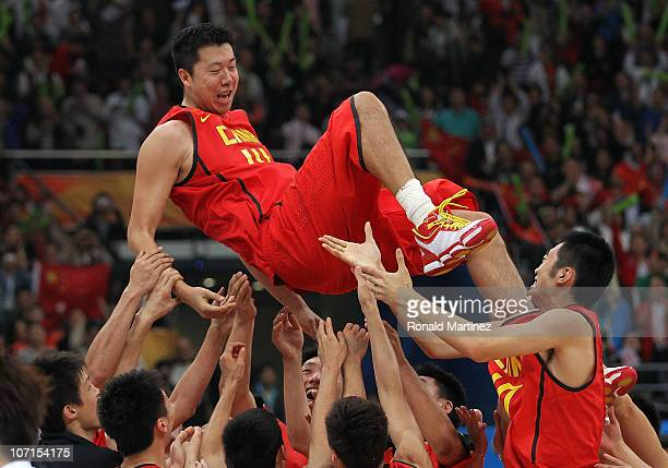Wang Zhizhi of China is lifted in the air after China wins the gold medal by defeating South Korea 7771 in the men's gold medal basketball game at...