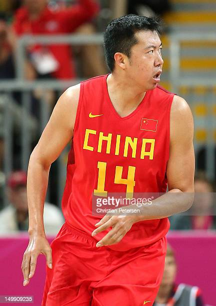 Wang Zhizhi of China reacts after he dunked the ball in the first half against Great Britain during the Men's Basketball Preliminary Round match on...