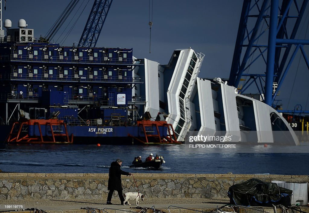 A waoman with her dog pass near the Costa Concordia cruise ship laying aground near the port on January 8, 2013 on the Italian island of Giglio. Works are going ahead after almost a year ago, on January 13, 2012, the giant Italian cruise ship Costa Concordia ran aground near a Tuscan island and pitched leaving 32 people dead.