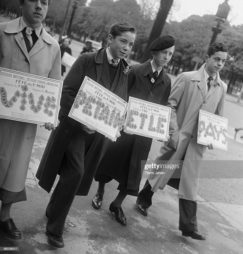 War 1939-1945. Occupation. The May 1st, 1941 in Paris. Young Petain supporters seller of badges of the marshal.