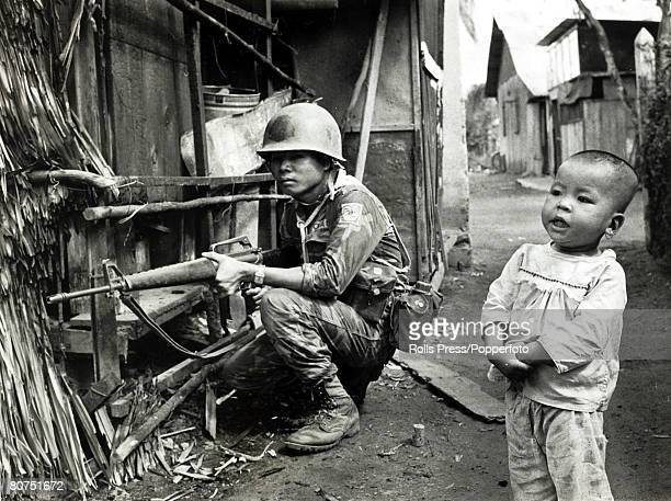 1968 South Vietnam A fearless youngster oblivious to danger stands alongside a crouching South Vietnamese soldier in a village street