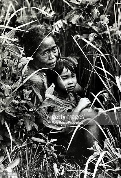 circa 1968 Chu Lai South Vietnam An old Vietnamese woman and her grandchild take cover in the fields as a battle ensues around them