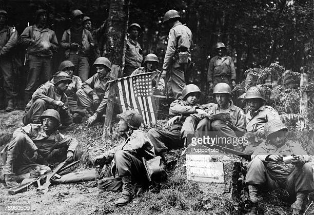 September 1944 American soldiers relaxing beside the Stars and Stripes flag the first time it had been raised on German soil as the advance had just...