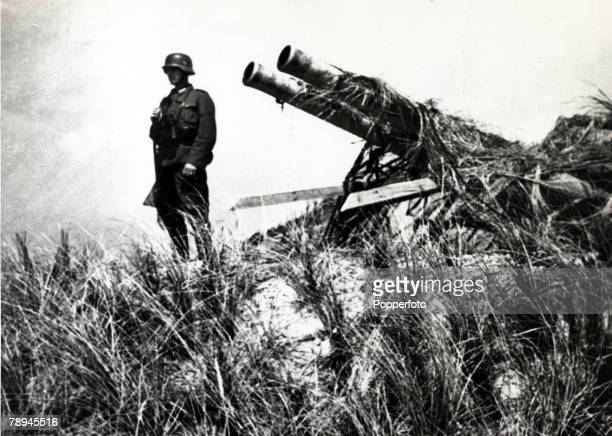 May 1940 A German soldier stands guard over a captured Dutch gun on the island of Texel Germany invaded Belgium Holland and Luxembourg in May 1940...