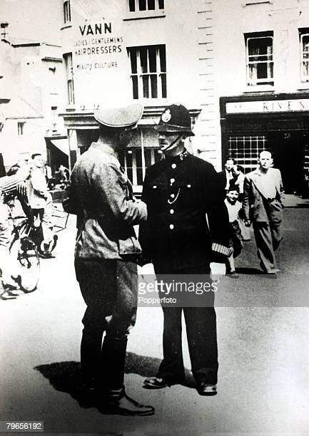 September 1940 The Occupation of the Channel Islands A German soldier talking to a man dressed in the uniform of a British policeman on Jersey...