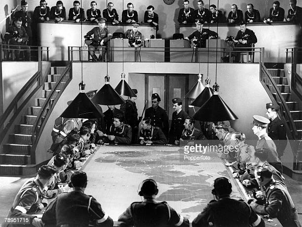 circa 1940 A British operations room crowded with military personel poring over a map of Great Britain