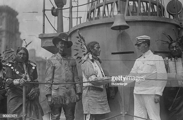 War Bonneted Native American shakes hands with the Commander of the 'Recruit' a facsimile Battleship constructed in the center of Manhattan to aid in...