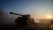 War Concept. Military silhouettes fighting scene on war fog sky background, World War Soldiers Silhouettes Below Cloudy Skyline at sunset. Attack scene. Armored vehicles. German tank in action