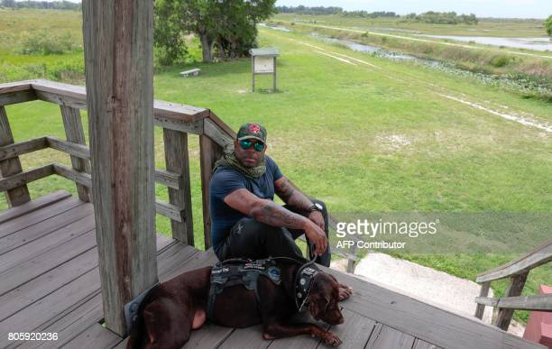 War veteran Chad Brownand his service dog Axe take a break at the Arthur R Marshall Loxahatchee National Wildlife Refugee in Boynton Beach Florida on...