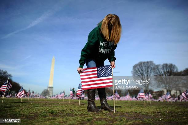 A war veteran helps set up 1892 American flags on the National Mall in Washington DC on March 27 2014 The Iraq and Afghanistan veterans installed the...