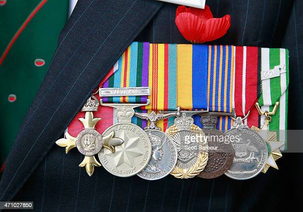 A war veteran's military service medals are displayed next to a poppy on his jacket as he attends the 2015 Dawn Service on ANZAC Day at the Shrine of...
