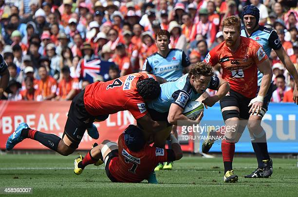 NSW Waratahs' Michael Hooper is tackled by Faatiga Lemalu and Taiyo Ando of the Sunwolves during their Super Rugby match in Tokyo on July 2 2016 /...