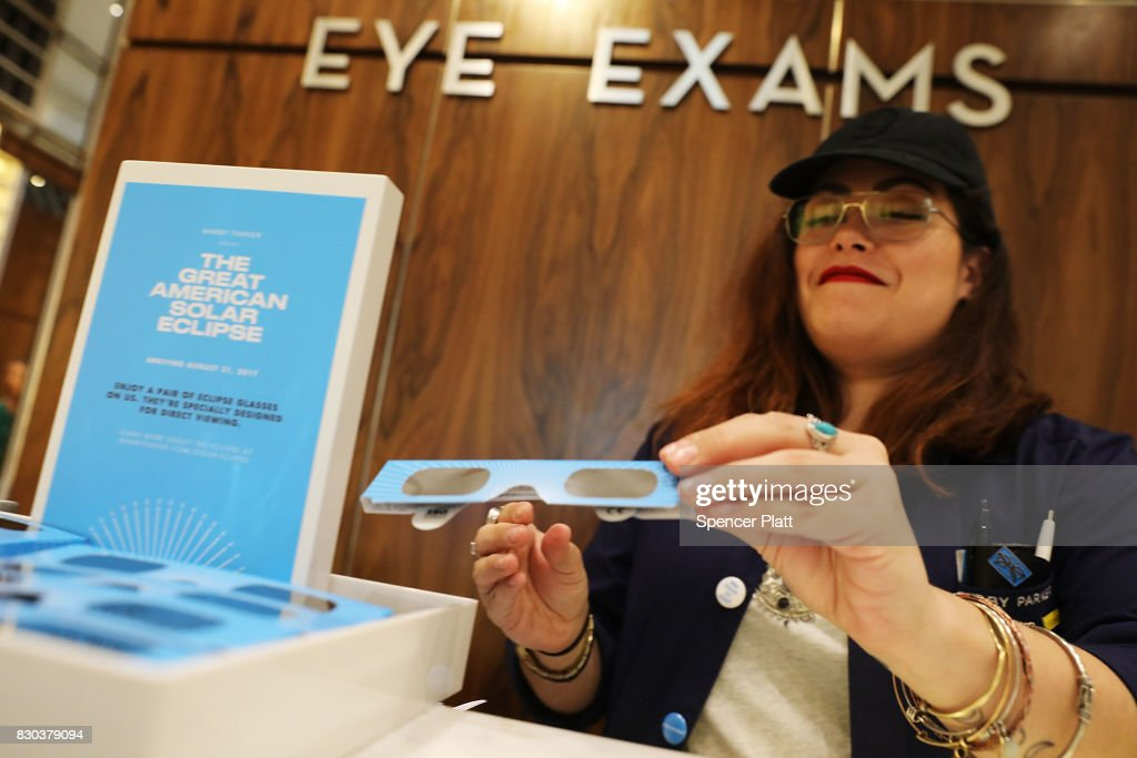 Warby Parker employee Gabi Rivera arranges pairs of solar eclipse glasses that the eyeglass store is giving out for free on August 11, 2017 in New York City. To view the upcoming total solar eclipse on August 21 eye protection is essential. The designer eyeglass store expects to give out thousands of the glasses before the event.