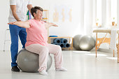 Elderly senior ward trying to maintain balance while sitting on a grey fit ball while being supported by physiatrist